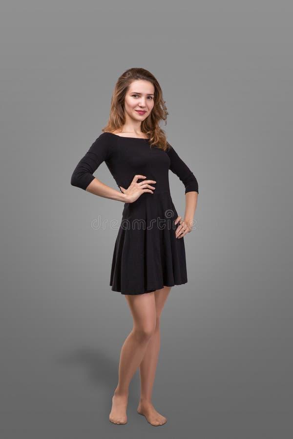 Mujer hermosa que se coloca en un vestido negro sobre fondo gris imagen de archivo