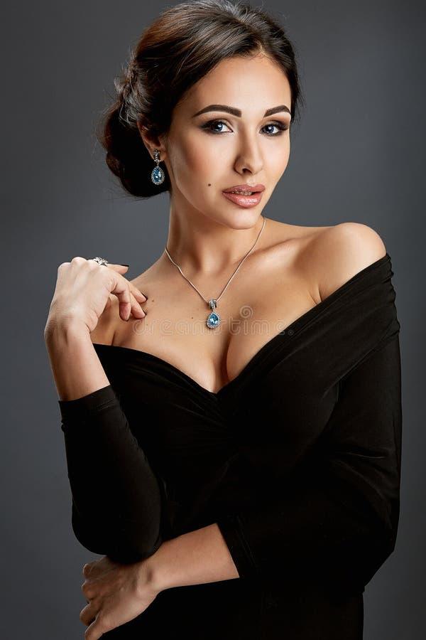 Mujer hermosa que se coloca en un vestido negro sobre fondo gris imagenes de archivo