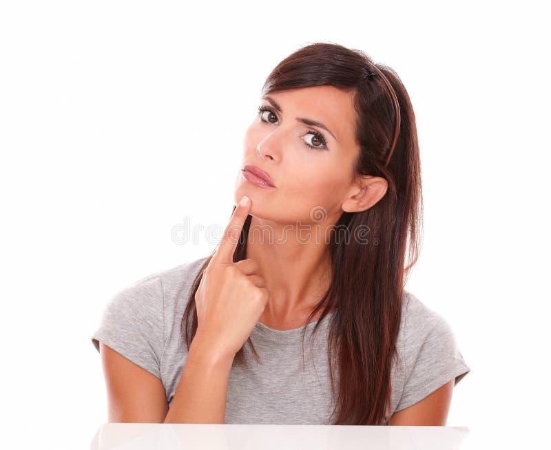 Mujer hermosa que se pregunta con su finger en la barbilla imagen de archivo