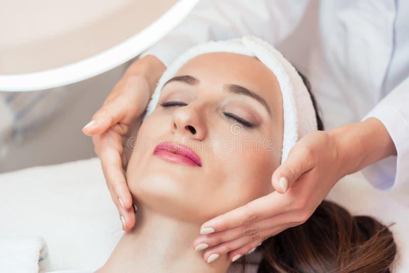 Mujer hermosa que se relaja durante el masaje facial para el rejuvenecimiento foto de archivo libre de regalías
