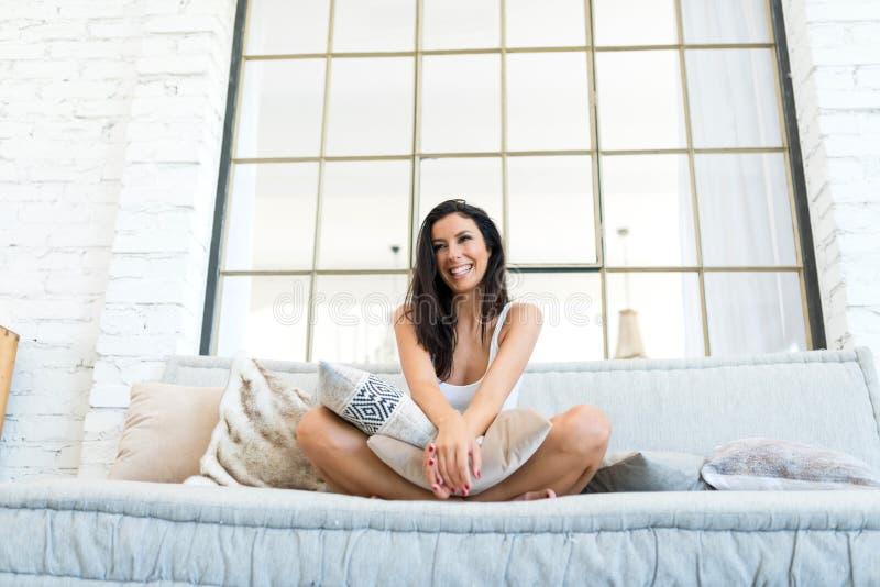 Mujer hermosa que se relaja en casa en el sofá foto de archivo libre de regalías