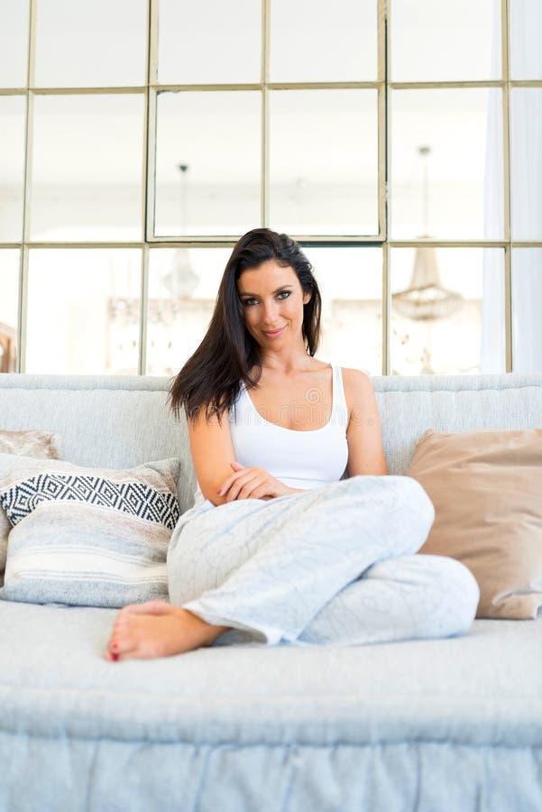 Mujer hermosa que se relaja en casa en el sofá foto de archivo