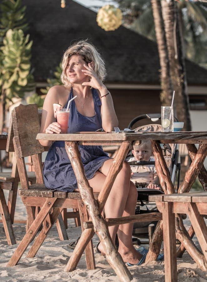 Mujer hermosa que se relaja en el restaurante de la playa foto de archivo libre de regalías