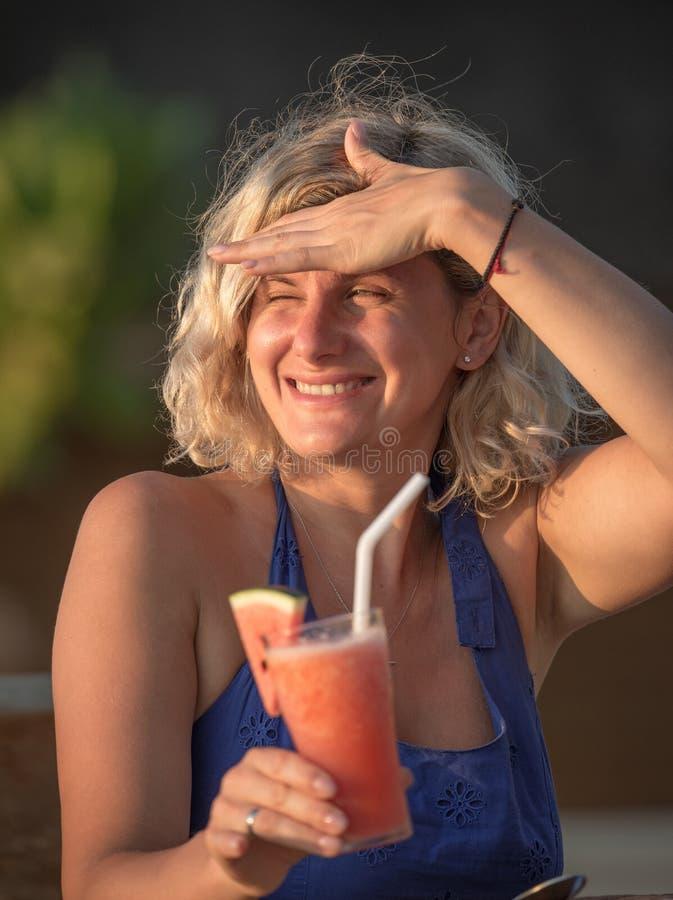Mujer hermosa que se relaja en el restaurante de la playa imagen de archivo