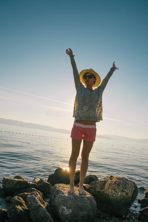 Mujer hermosa que se relaja en la playa Mar azul azul Vacaciones de verano Sombrero de paja La chica joven disfruta de vacaciones fotografía de archivo libre de regalías