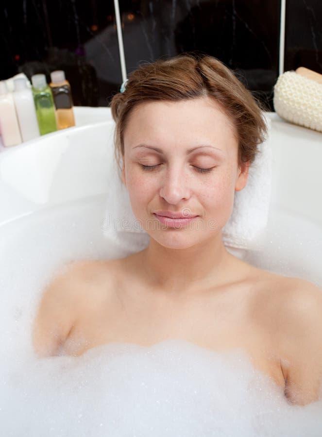 Mujer hermosa que se relaja en un baño de burbuja imágenes de archivo libres de regalías