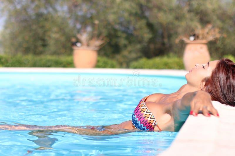 Mujer hermosa que se relaja en una piscina imagen de archivo
