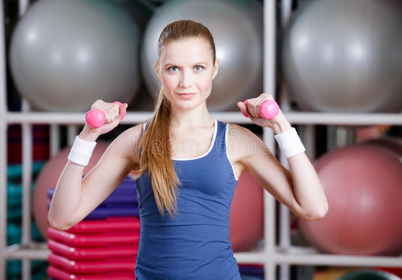 Mujer hermosa que se resuelve con pesas de gimnasia foto de archivo libre de regalías