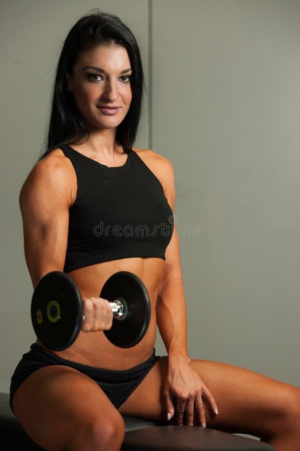Mujer hermosa que se resuelve con pesas de gimnasia en aptitud fotografía de archivo libre de regalías