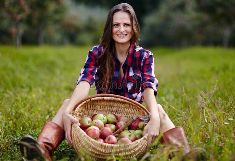 Mujer hermosa que se sienta cerca de una cesta de manzanas imágenes de archivo libres de regalías