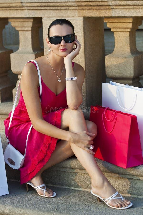 Mujer hermosa que se sienta con los bolsos de compras imagenes de archivo