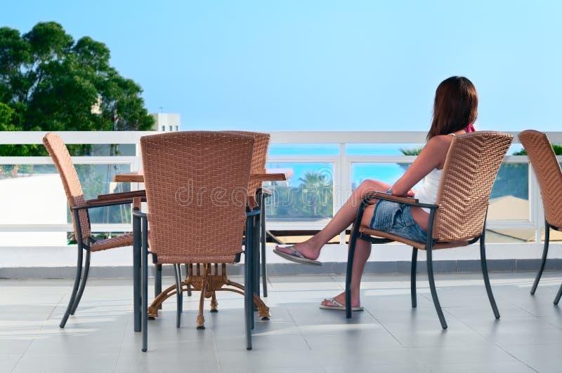 Mujer hermosa que se sienta en balcón imagenes de archivo