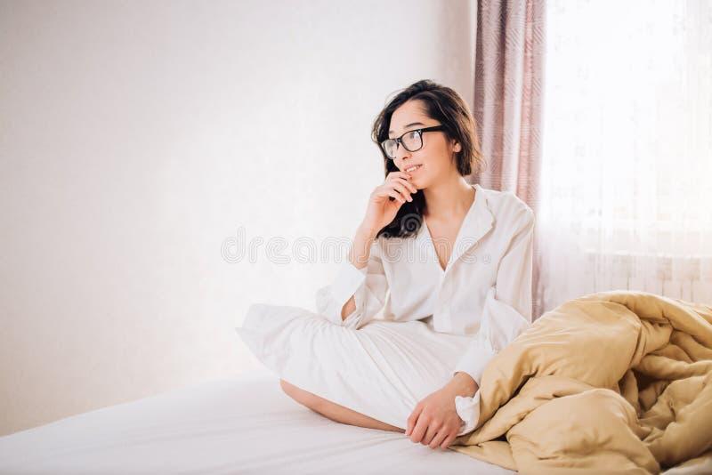 Mujer hermosa que se sienta en cama por mañana fotos de archivo