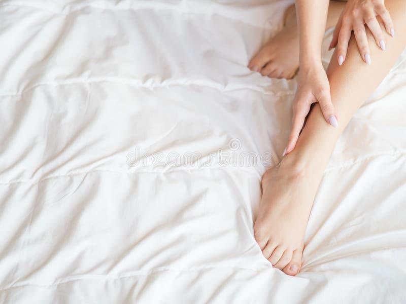 Mujer hermosa que se sienta en cama y que toca su piel en sus piernas imagen de archivo
