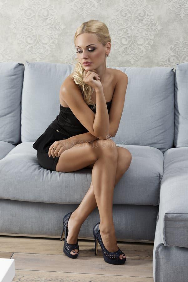 Mujer hermosa que se sienta en el sofá y que mira abajo fotografía de archivo libre de regalías