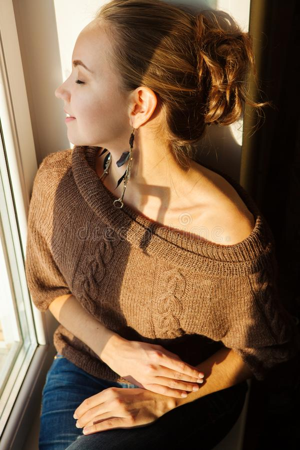 Mujer hermosa que se sienta en el travesaño de la ventana y que mira en alguna parte foto de archivo libre de regalías