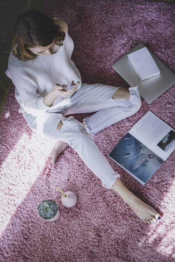 Mujer hermosa que se sienta en la alfombra rosada en el piso en la sala de estar de color claro moderna y que usa los artilugios  fotografía de archivo libre de regalías