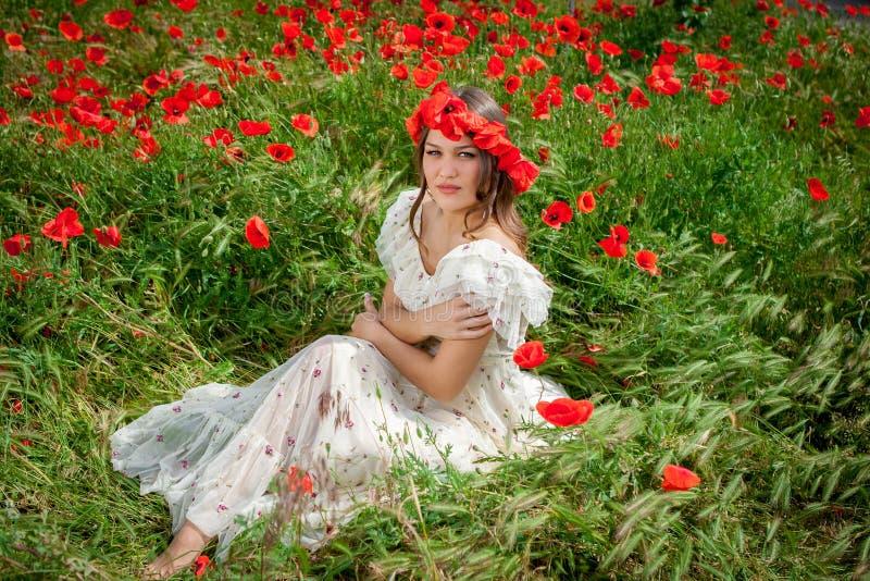 Mujer hermosa que se sienta en la flor de la amapola foto de archivo