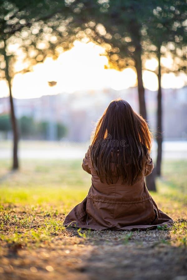 Mujer hermosa que se sienta en la hierba en un parque durante puesta del sol de la caída imagen de archivo libre de regalías