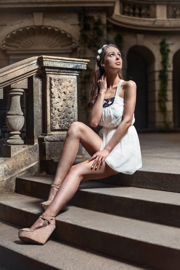 Mujer hermosa que se sienta en las escaleras viejas en el castillo fotos de archivo libres de regalías