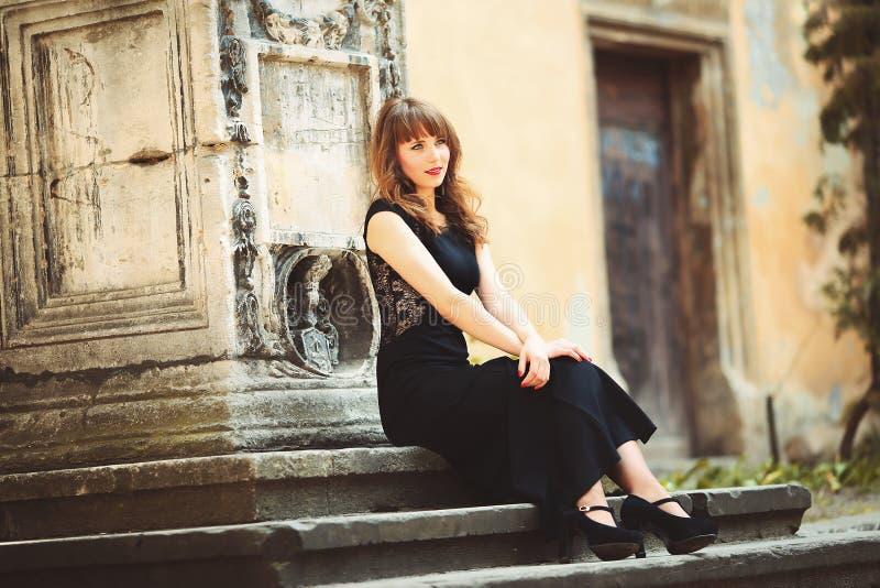 Mujer hermosa que se sienta en las escaleras viejas en el castillo foto de archivo