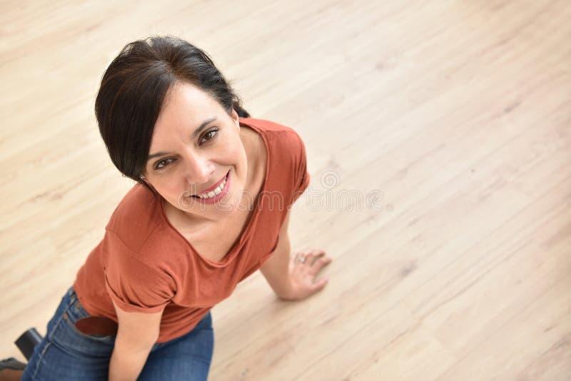 Mujer hermosa que se sienta en piso de madera foto de archivo
