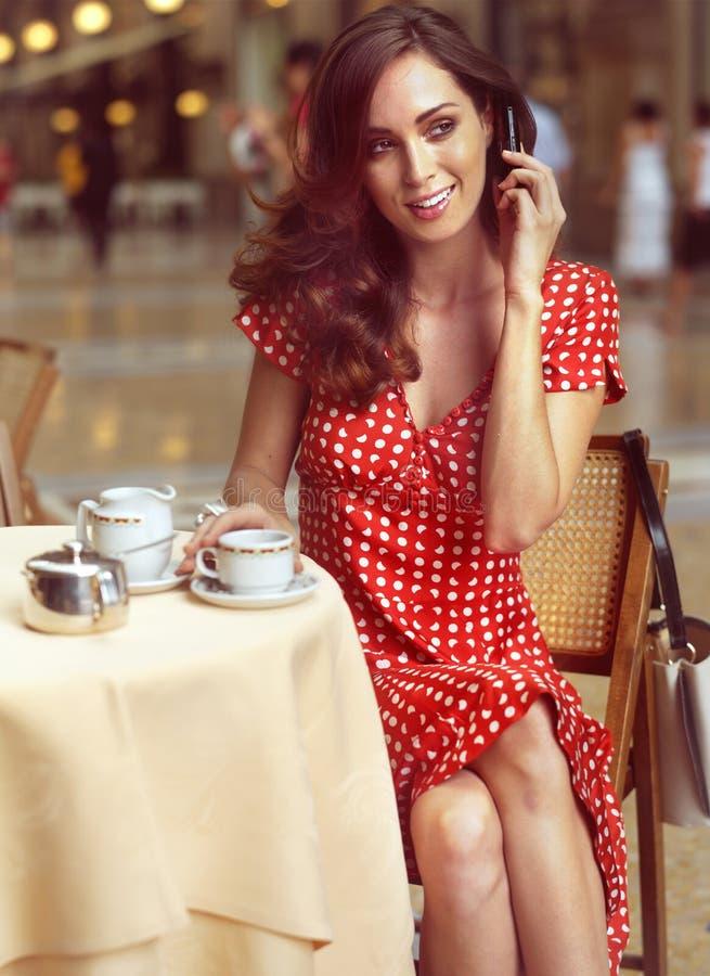 Mujer hermosa que se sienta en un café con el móvil imagenes de archivo