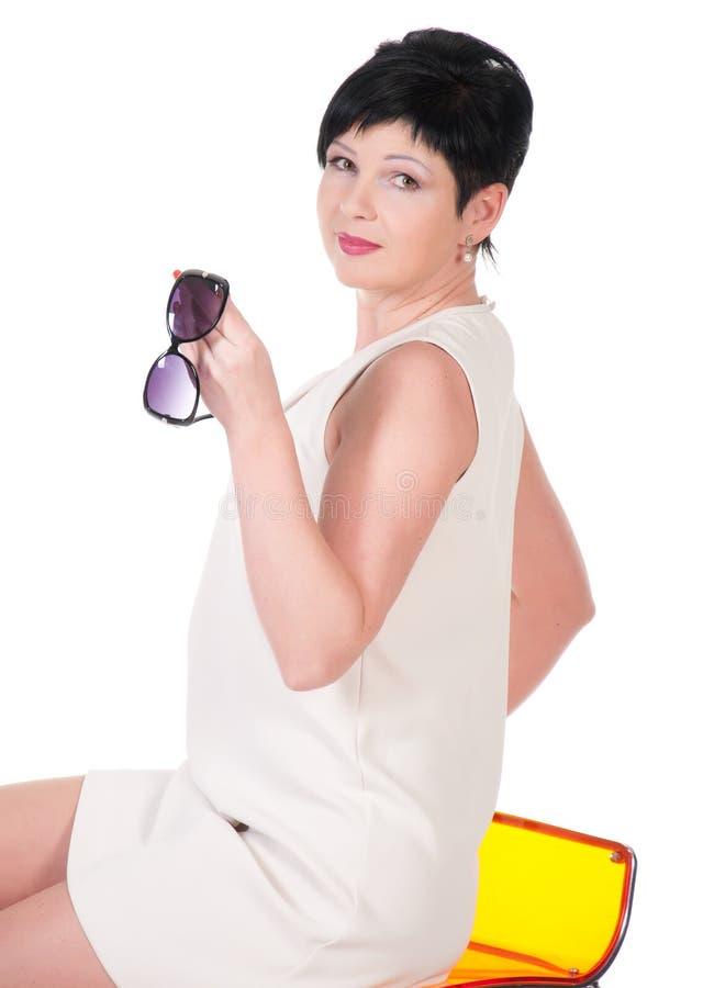Mujer hermosa que se sienta en una silla con las gafas de sol fotos de archivo libres de regalías