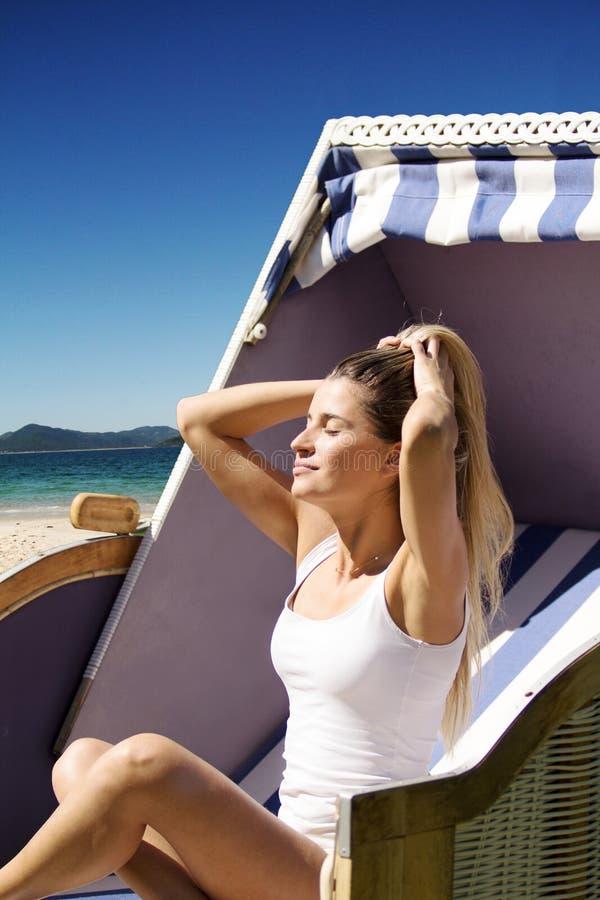 Mujer hermosa que se sienta en una silla de mimbre que goza del sol en el th imagen de archivo