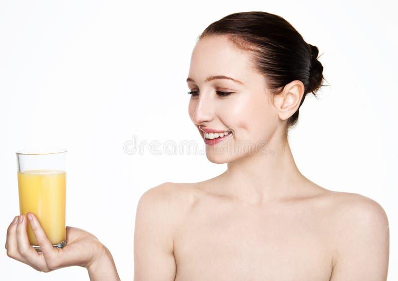 Mujer hermosa que se sostiene de cristal con el zumo de naranja fotos de archivo libres de regalías