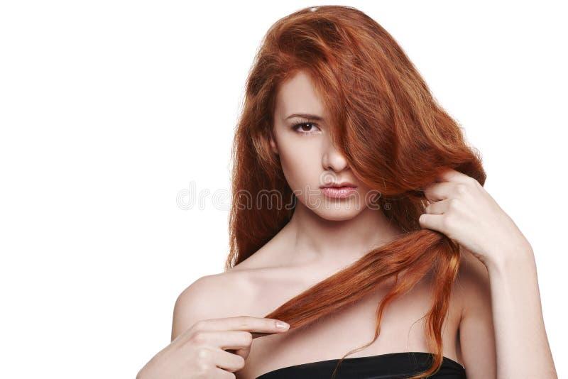 Mujer hermosa que se sostiene el pelo rojo disponible foto de archivo libre de regalías