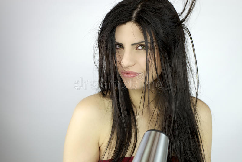 Mujer hermosa que seca el pelo largo foto de archivo
