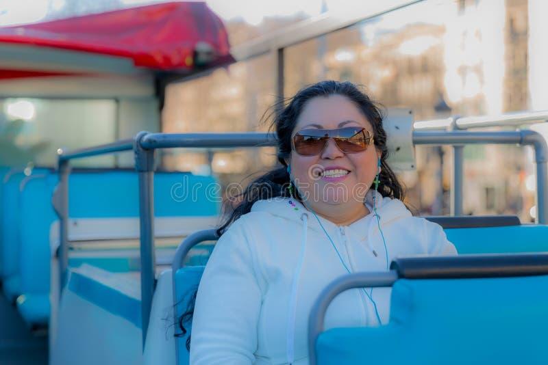 Mujer hermosa que sonríe en un autobús turístico que goza de la ciudad fotos de archivo