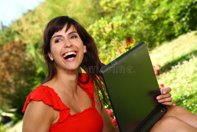 Mujer hermosa que sonríe sosteniendo un ordenador que disfruta de día soleado imagen de archivo