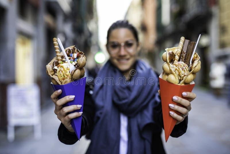 Mujer hermosa que sostiene dos galletas de la burbuja con helado y caramelos en conos de papel azules y rojos con irreconocible b imágenes de archivo libres de regalías