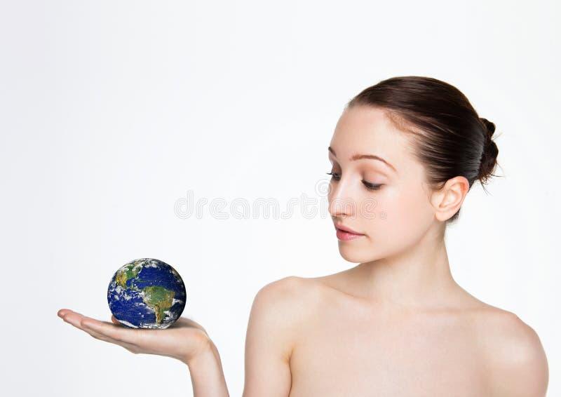 Mujer hermosa que sostiene el globo de la tierra en su brazo imagen de archivo