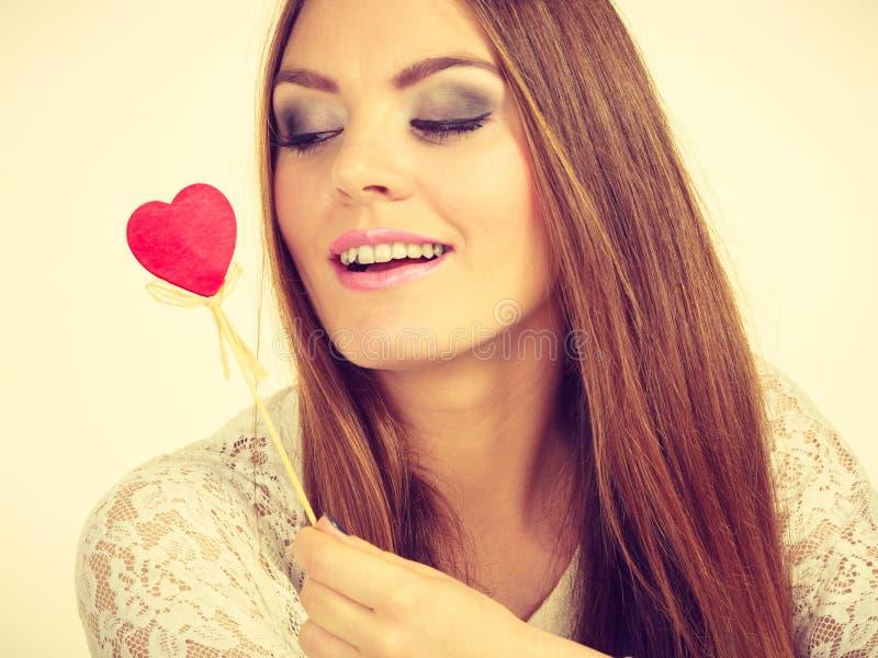 Mujer hermosa que sostiene el palillo en forma de coraz?n de la mano fotos de archivo