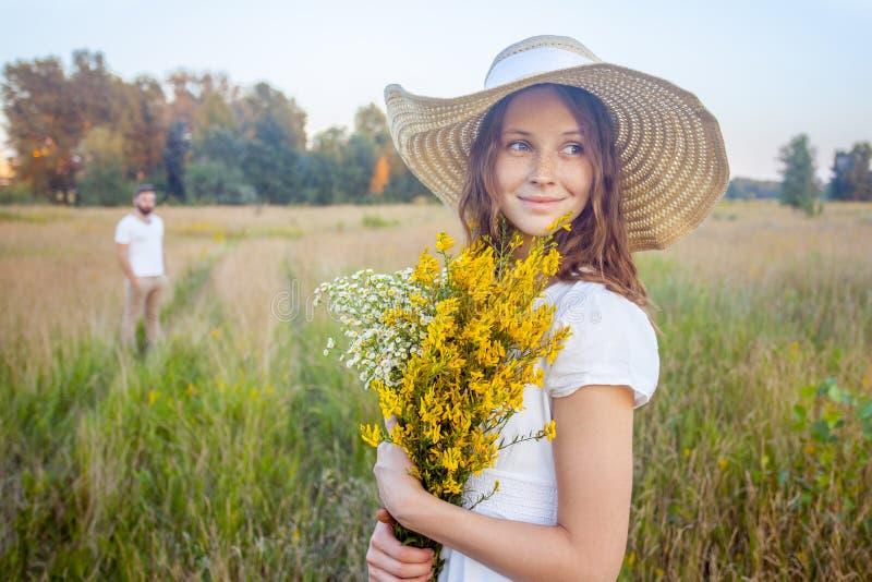 Mujer hermosa que sostiene el ramo de flores amarillas y que mira la cámara con su novio en fondo imagen de archivo