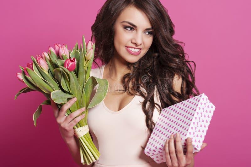 Mujer hermosa que sostiene el regalo de la caja del ANG de las flores fotos de archivo