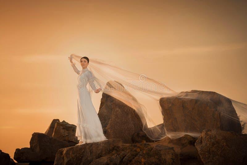 Mujer hermosa que sostiene la bufanda blanca en fondo de la puesta del sol imagenes de archivo