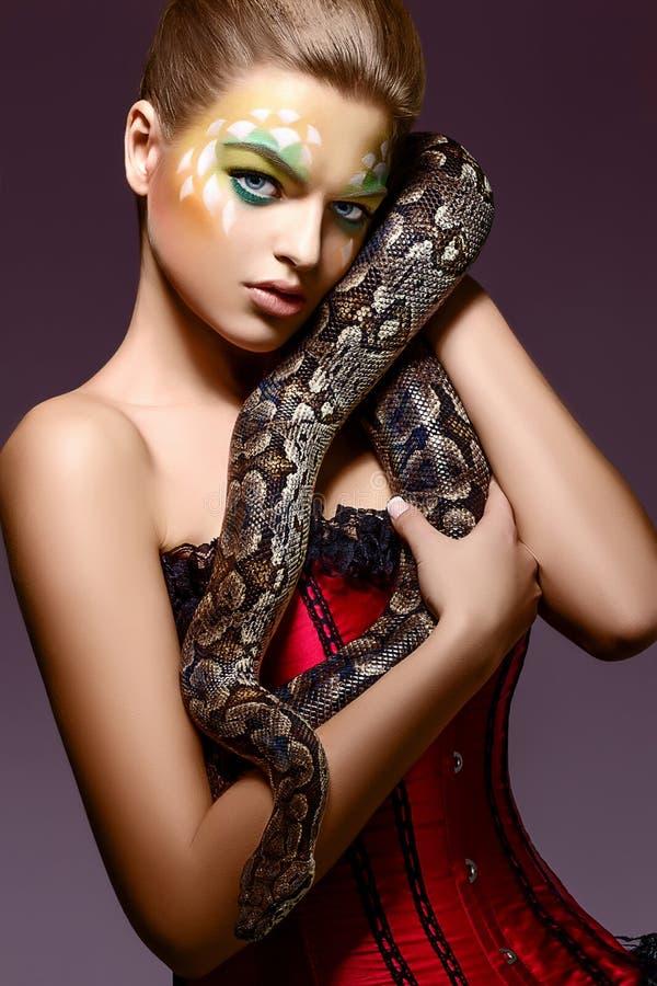 Mujer hermosa que sostiene la serpiente en manos - funcionamiento del pitón fotografía de archivo libre de regalías