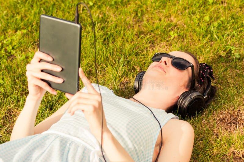 Mujer hermosa que sostiene la tableta digital en parque el día soleado imagenes de archivo