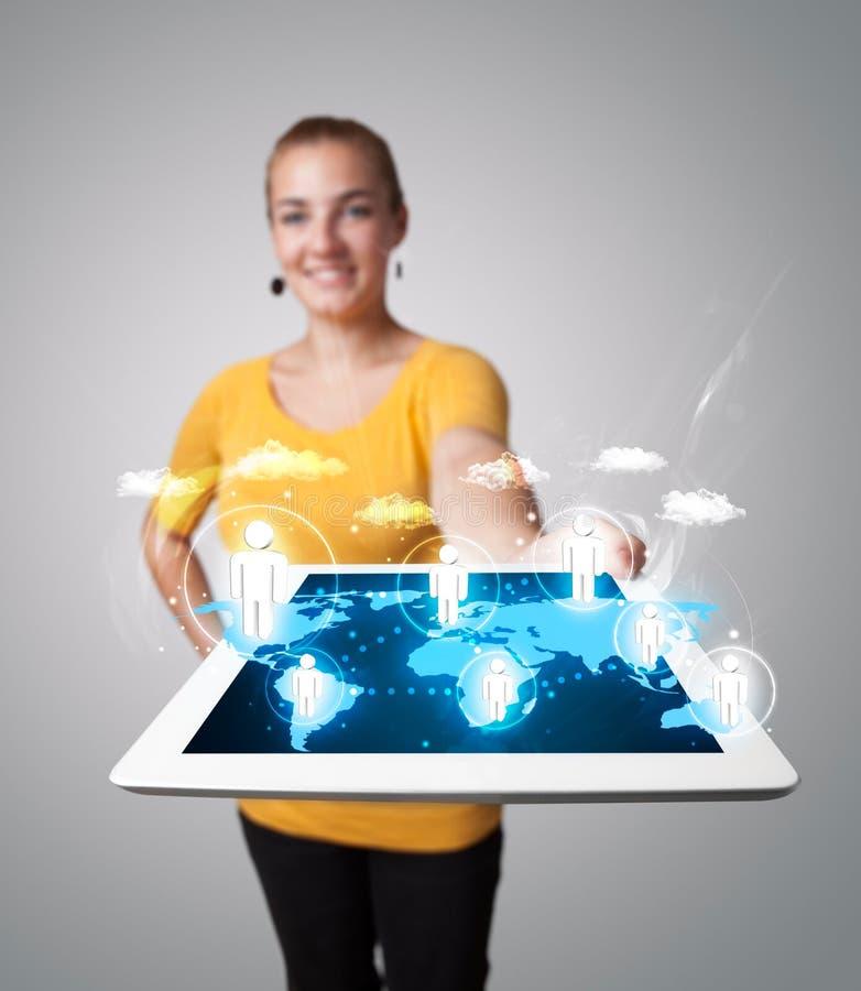 Mujer hermosa que sostiene la tableta moderna con los iconos sociales imagen de archivo libre de regalías