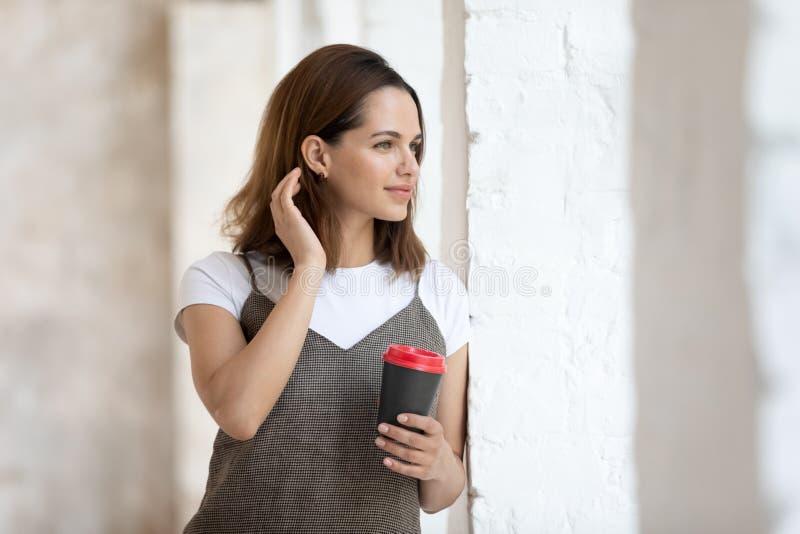 Mujer hermosa que sostiene la taza de café del papel que mira hacia fuera la ventana fotografía de archivo libre de regalías