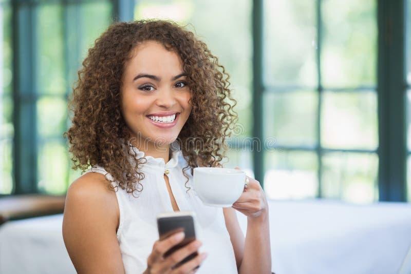 Mujer hermosa que sostiene la taza de café y que usa el teléfono móvil imágenes de archivo libres de regalías