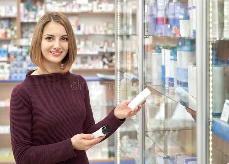 Mujer hermosa que sostiene las botellas cosméticas en farmacia fotografía de archivo libre de regalías