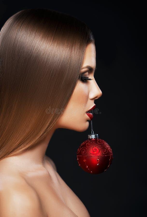 Mujer hermosa que sostiene un ornamento de la Navidad con los dientes foto de archivo libre de regalías