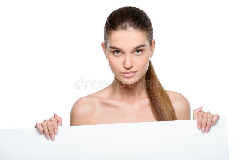 Mujer hermosa que sostiene una cartelera en blanco imagen de archivo libre de regalías