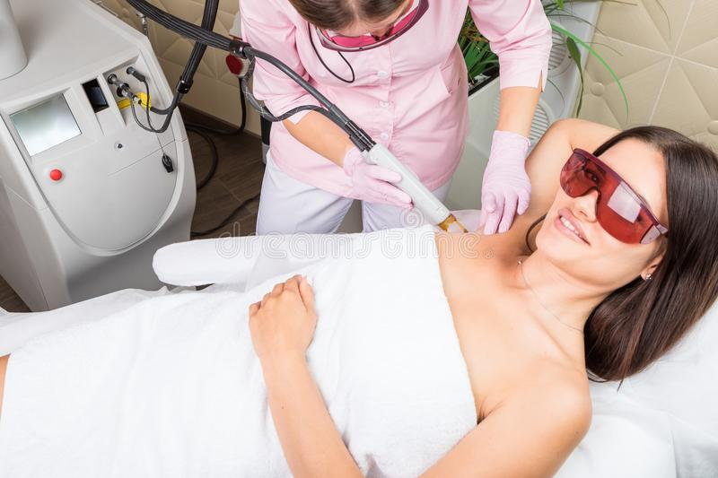 Mujer hermosa que tiene retiro del pelo del laser del axila en clínica profesional de la cosmetología Equipo profesional foto de archivo
