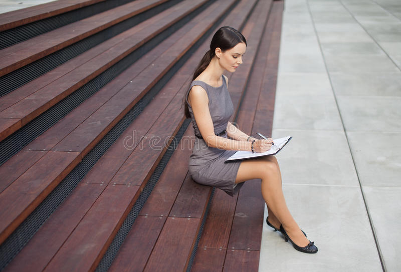 Mujer hermosa que toma notas foto de archivo